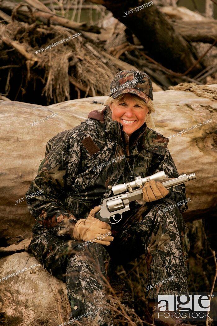 Imagen: Female big game hunter with a scoped handgun.