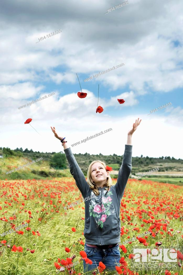 Stock Photo: Blonde teen girl throwing flowers in the wind.