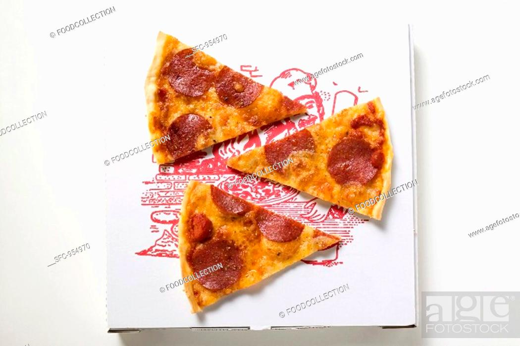 Stock Photo: Three slices of pepperoni pizza on pizza box.