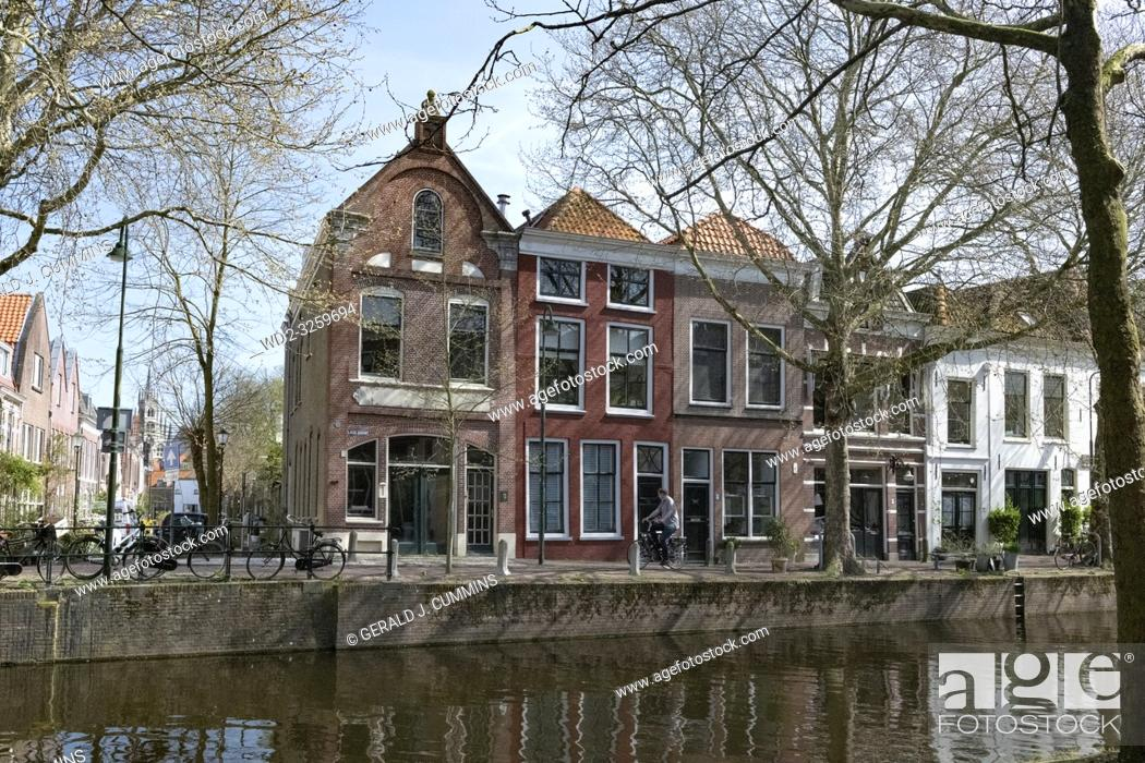 Stock Photo: Netherlands, Gouda, 2017, cyclist passing in front of traditional houses on the banks of a canel.