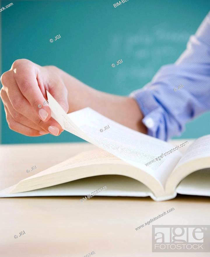 Stock Photo: Hand turning page in book.