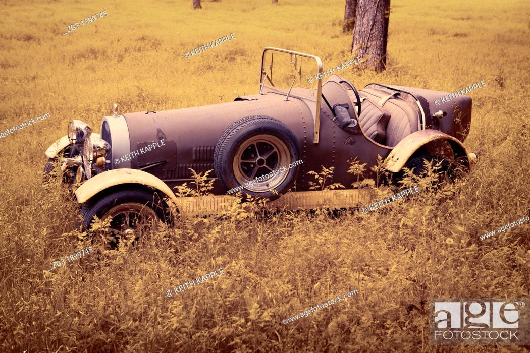 Stock Photo: Infrared image of an Old Abandoned Rusty Vintage Convertible Car in a field of weeds out in West Texas.