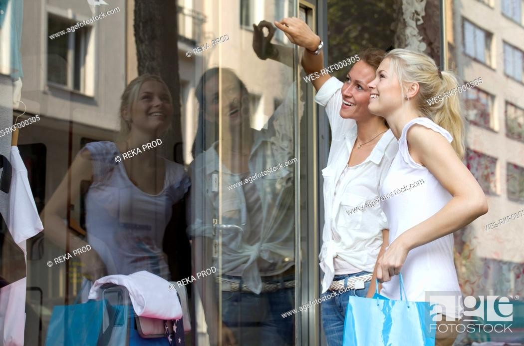 Stock Photo: Germany, North Rhine Westphalia, Cologne, Young women at window shopping, smiling.