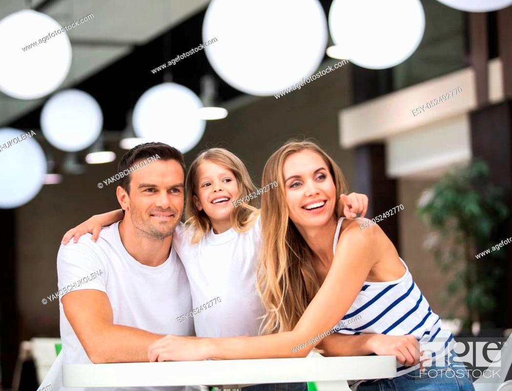 Stock Photo: Waist up portrait of joyful couple sitting with child in bar at table. Small girl is pointing with finger while smiling woman and man are looking sideways.