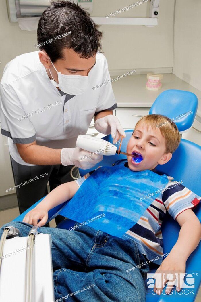 Imagen: Dentist examining a boy's teeth.
