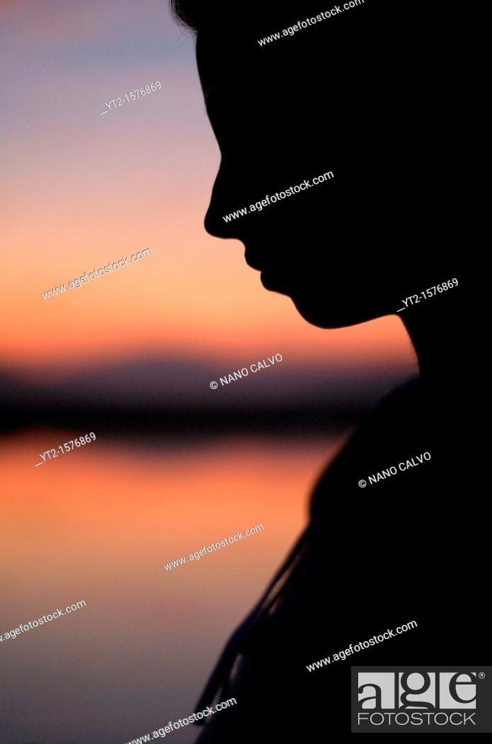 Stock Photo: Silhouette of an attractive young woman at sunset.