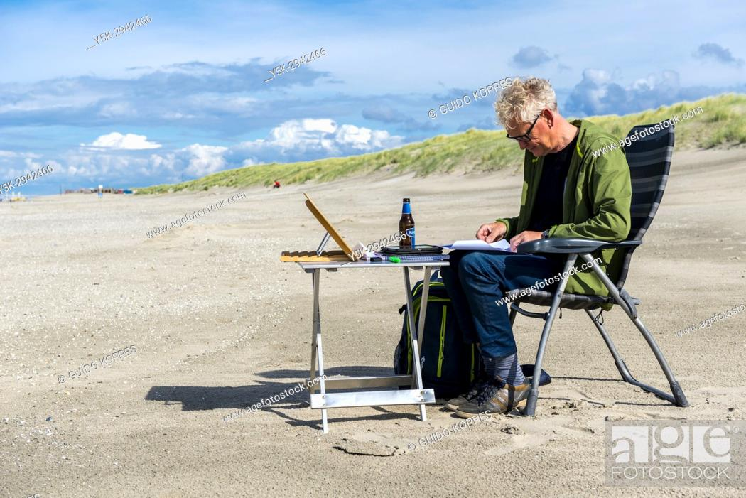 """Stock Photo: Hook of Holland, Netherlands. Mature adult male clerck reading his documents, while being """"""""installed"""""""" on the North Sea coastal beach."""