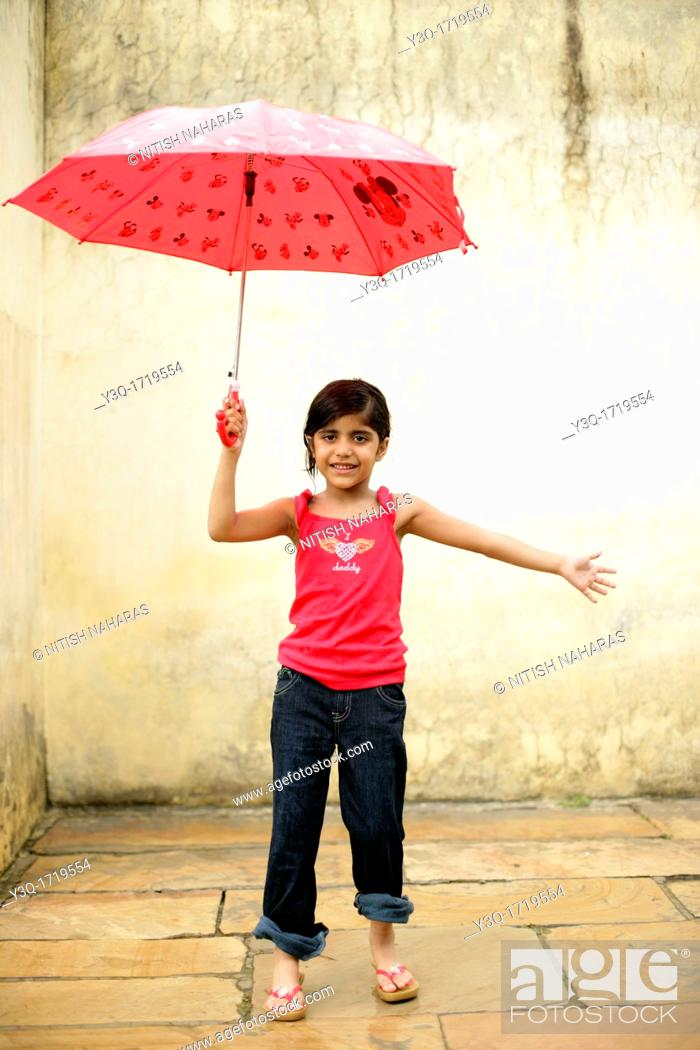 Stock Photo: Innocent young girl smiling in the rain while holding an umbrella.