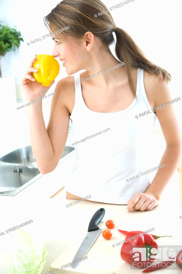 Stock Photo: woman in kitchen smelling ywllow pepper.