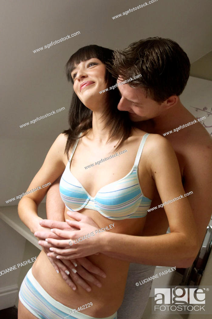 Stock Photo: young couple standing together, cuddling, smiling.