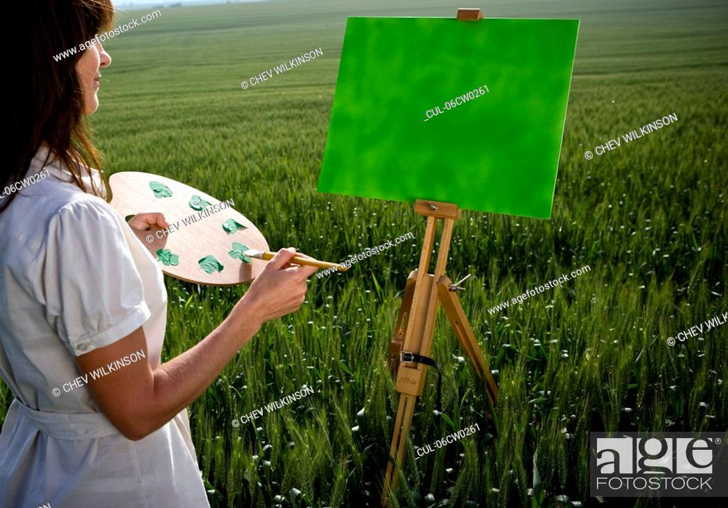 Stock Photo: Woman painting in wheat-field.