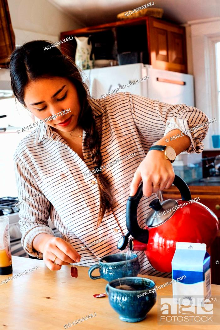 Stock Photo: Woman pouring water from stove top whistling kettle into teacup.