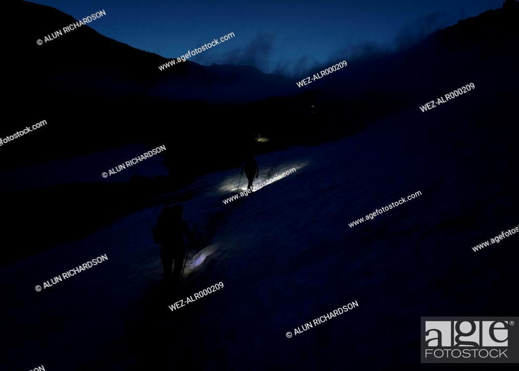 Imagen: Switzerland, Wallis, Saas-Grund, Pennine Alps, Weissmies, female mountaineer at night.