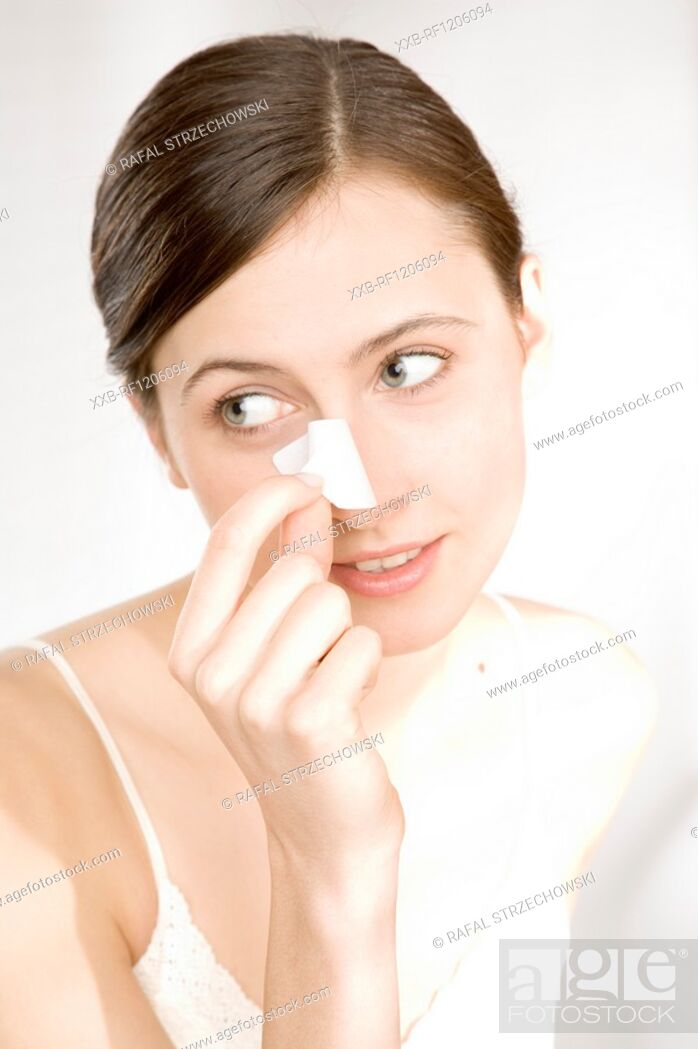 Stock Photo: woman taking off cleansing strip.