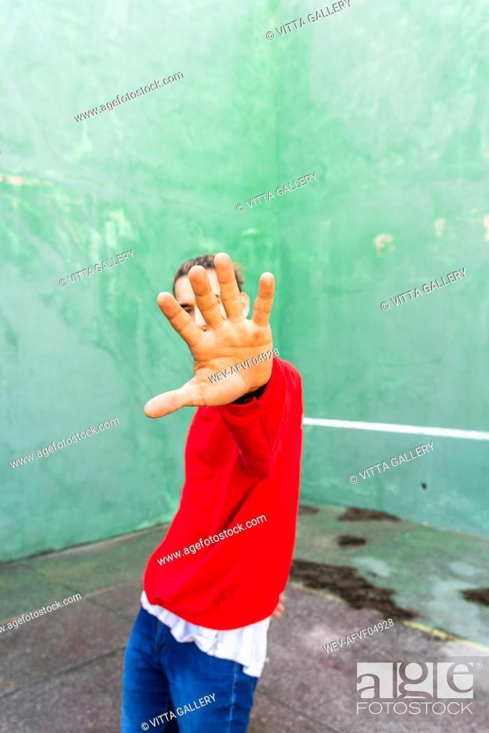 Stock Photo: Young man wearing red sweatshirt raising hand.