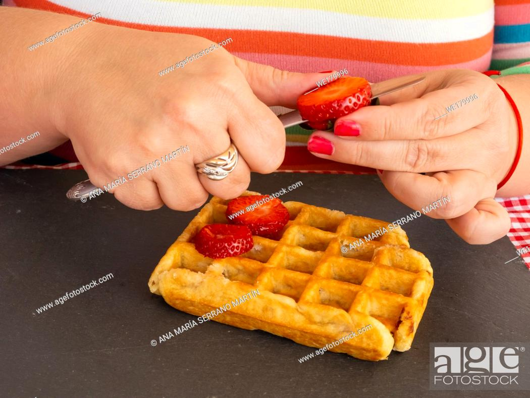 Imagen: A woman with red fingernails cutting a strawberry and placing it on a Belgian waffle.