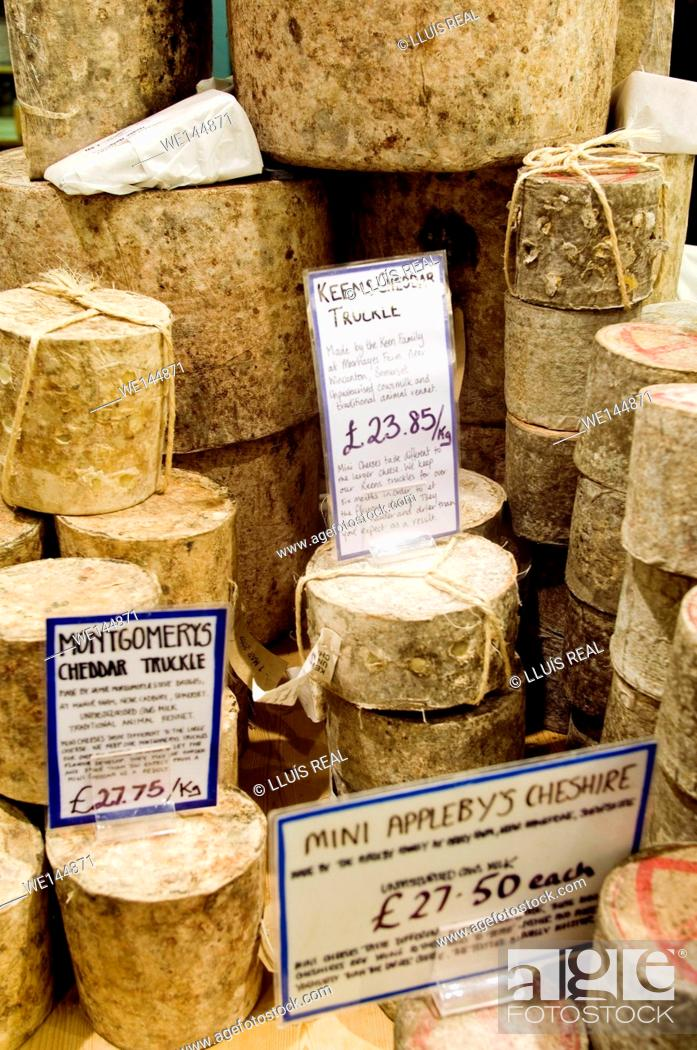 Stock Photo: Pile of different types of cheeses on a cheese store, Borought Market, Southwark, London, England, UK, Europe. Montgomerys Cheddar Truckle.