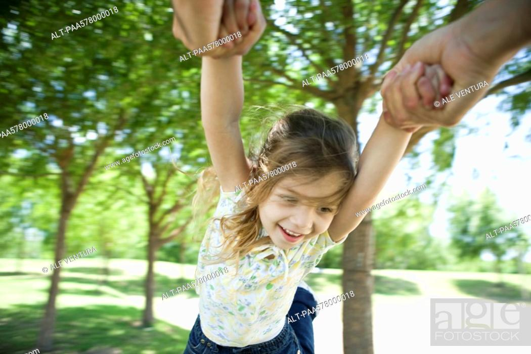 Stock Photo: Little girl being swung through air by her arms.