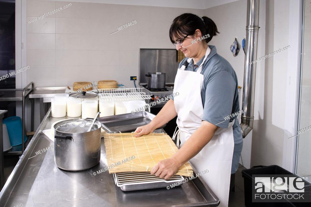 Stock Photo: Cheesemaker puts fresh cheese on the rush for a typical process.