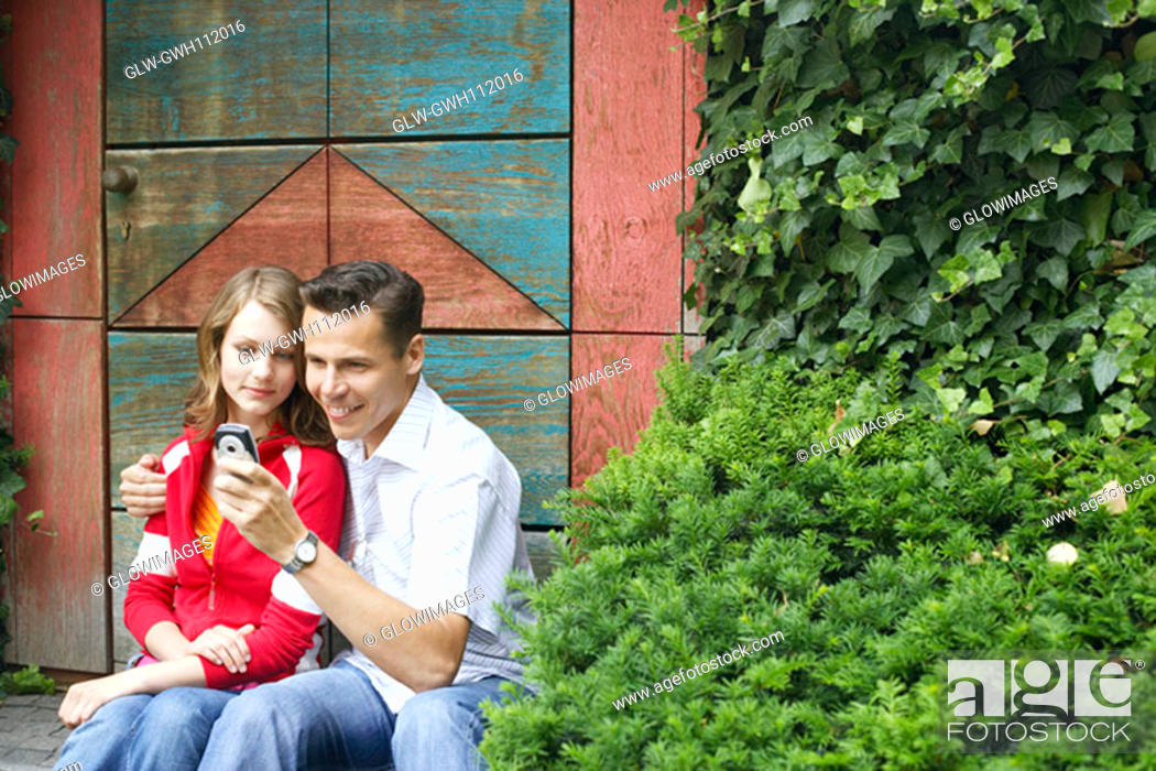 Stock Photo: Mid adult man and a teenage girl looking at a mobile phone.