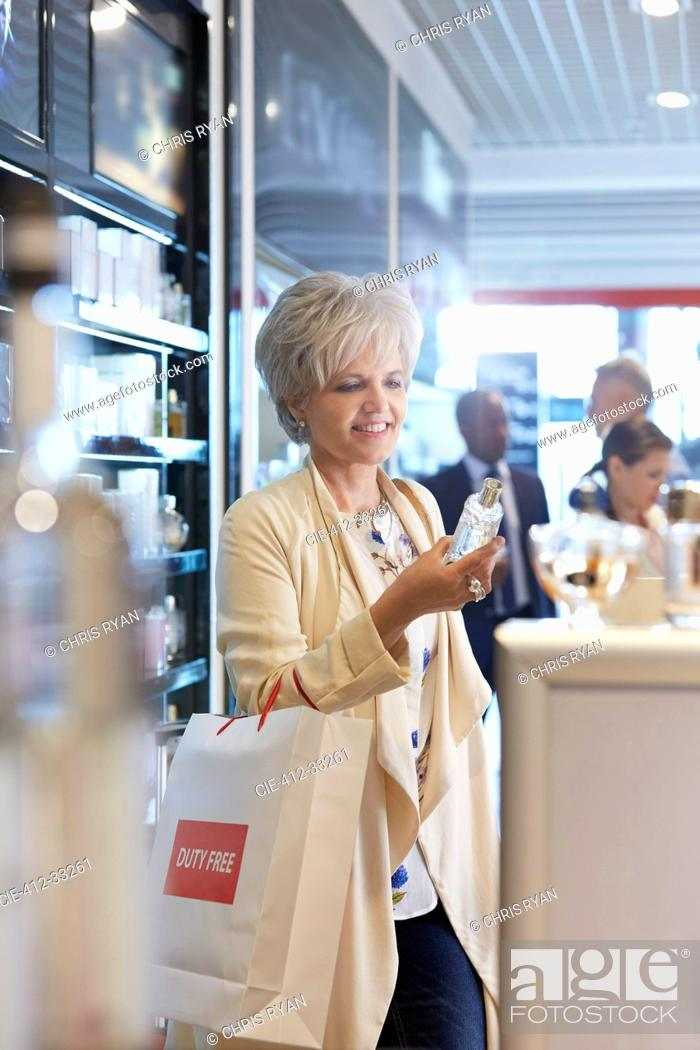 Stock Photo: Woman shopping for perfume in airport duty free shop.