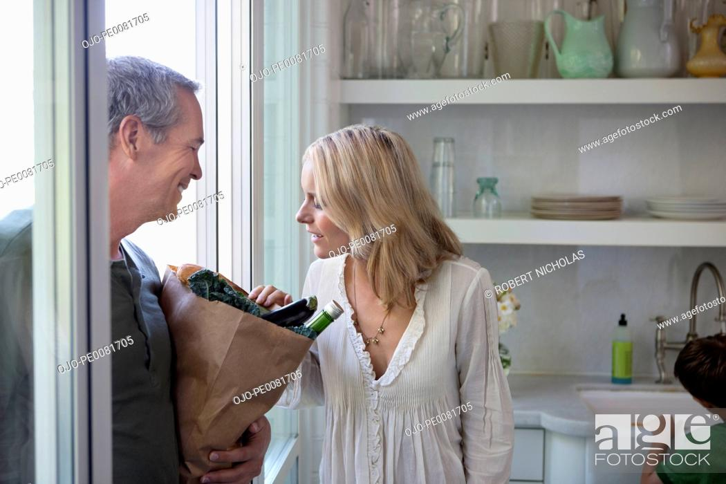 Stock Photo: Woman inspecting husband's groceries.