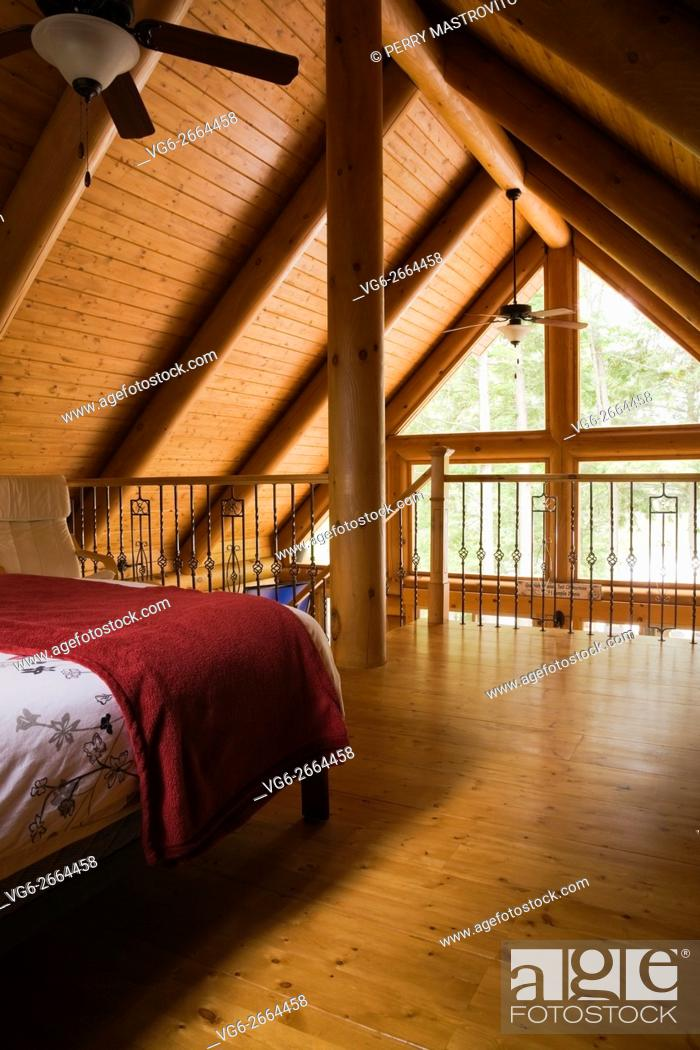 Stock Photo: Partial view of the master bedroom on the upstairs floor inside a residential log home, Laurentians, Quebec, Canada.
