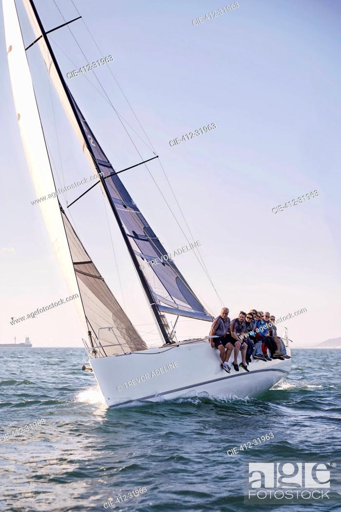 Imagen: Friends sailing on heeling sailboat on ocean under blue sky.