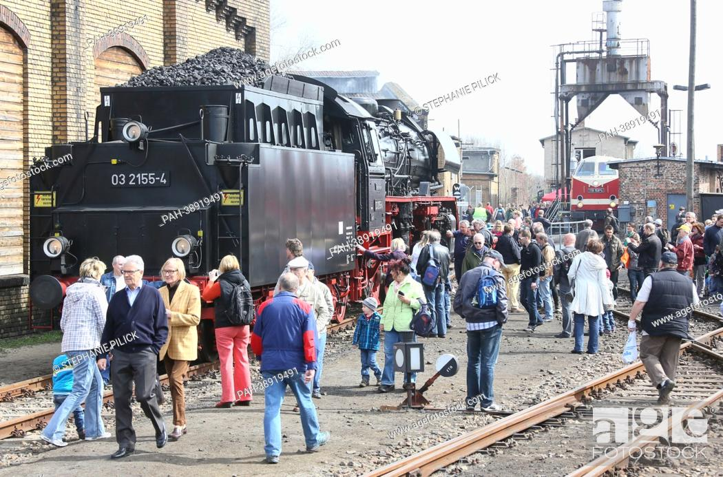 Stock Photo: Visitors walk past a historical locomotive at the rail yard Schöneweide in Berlin, Germany, 20 April 2013. More than 40 historical locomotives and cars are.