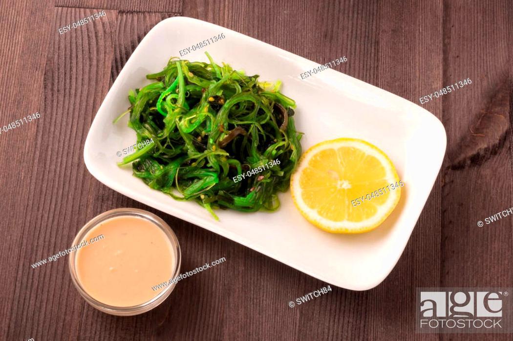 Stock Photo: Chukka salad on a white plate with walnut sauce and lemon. Tasty and healthy food.