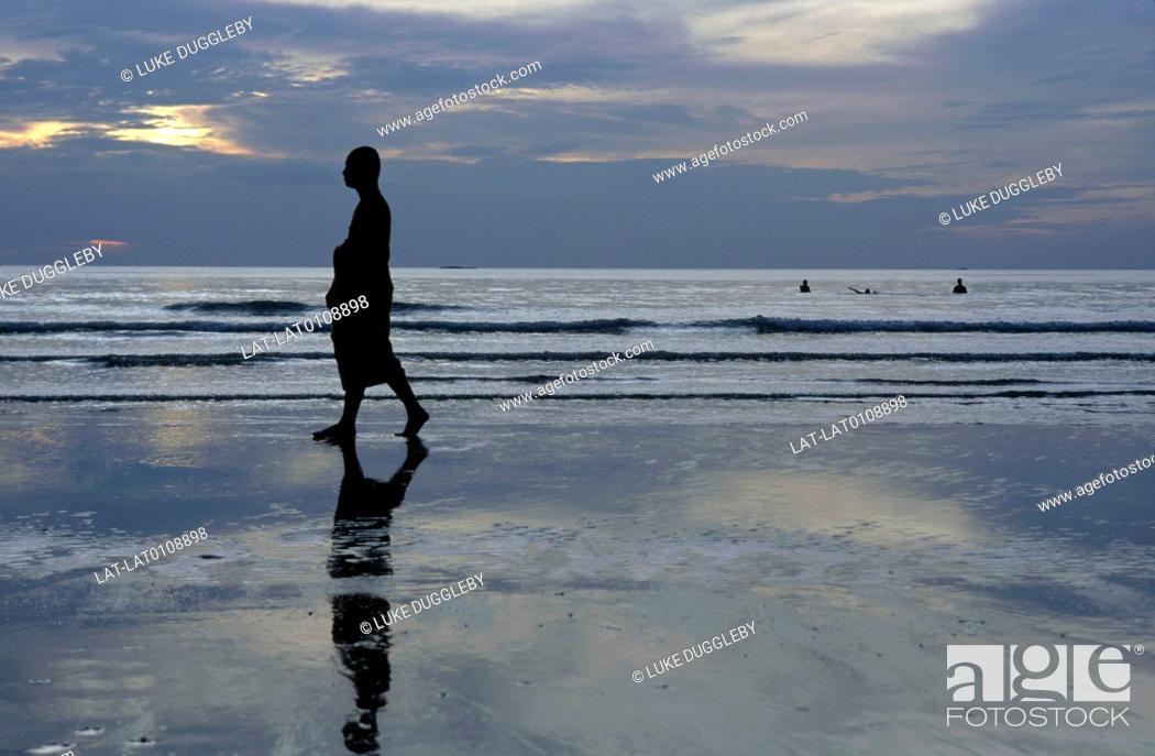 Imagen: National park. Beach. Thai Buddhist monk in long robe. Walking on sand. Sunset. Low light. Silhouette.