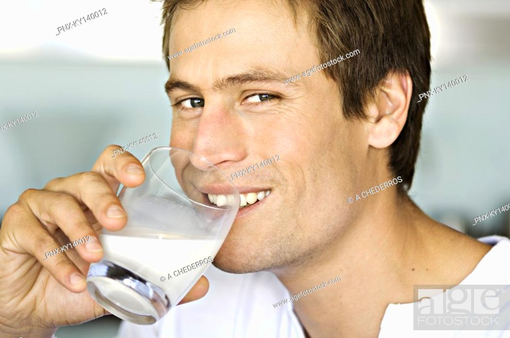Stock Photo: Portrait of a young man drnking glass of milk.