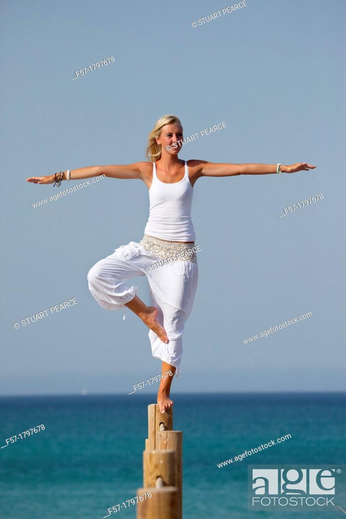 Stock Photo: Healthy young woman balancing on a wooden post.