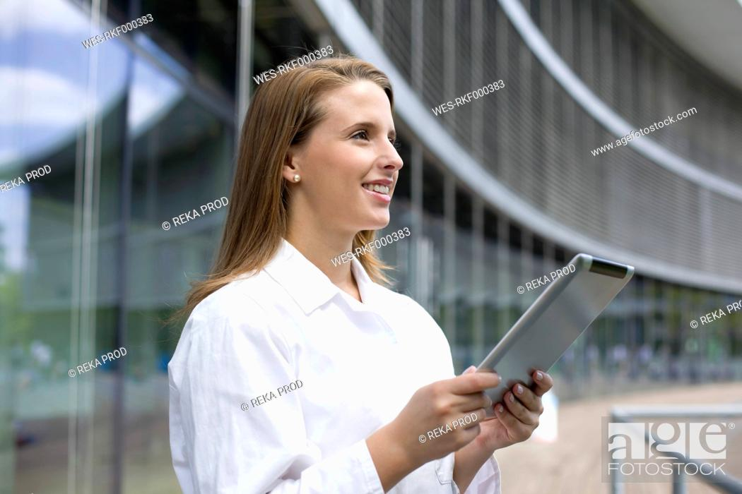 Stock Photo: Europe, Germany, North Rhine Westphalia, Duesseldorf, Medical student with digital tablet, smiling.