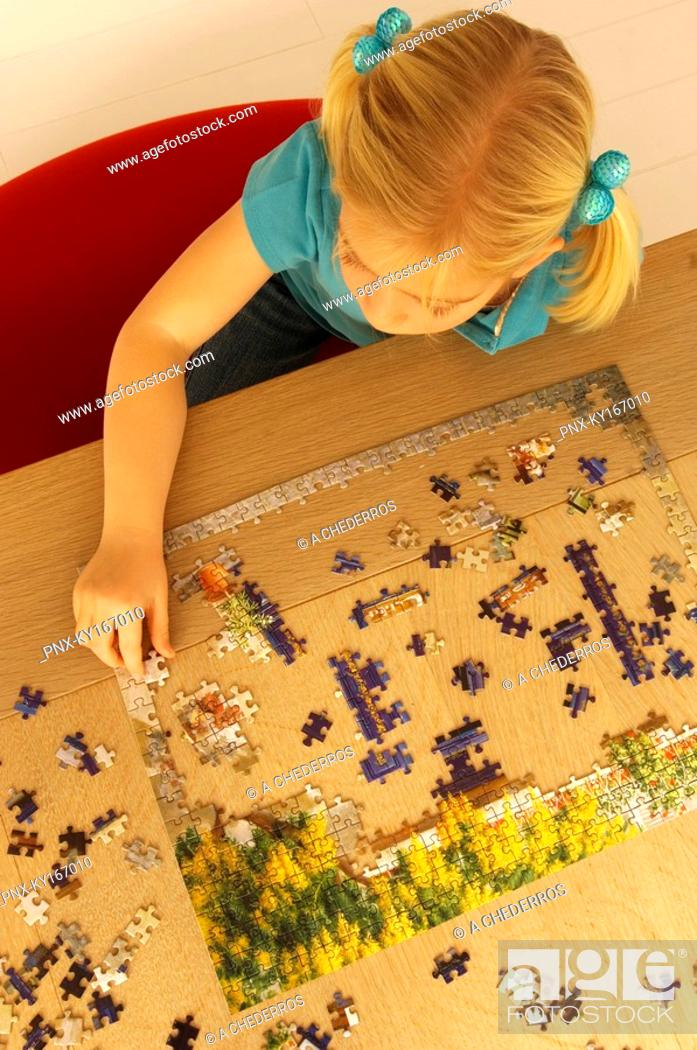 Stock Photo: High angle view of a girl playing a jigsaw puzzle.