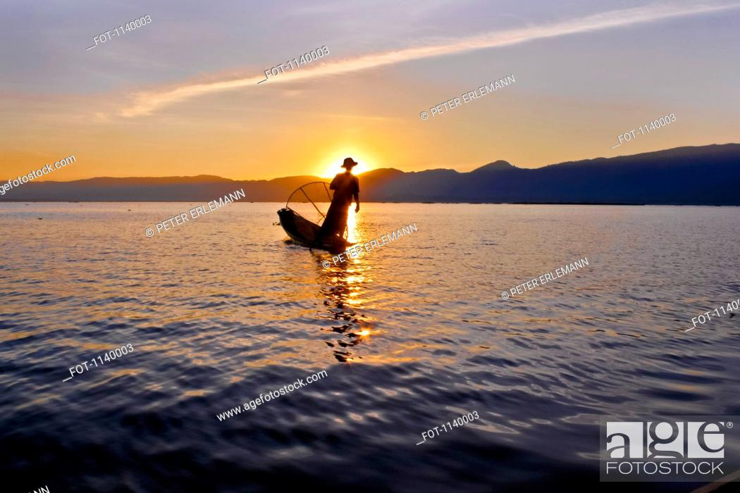 Stock Photo: Silhouette of a person on a boat, Inle Lake, Burma.