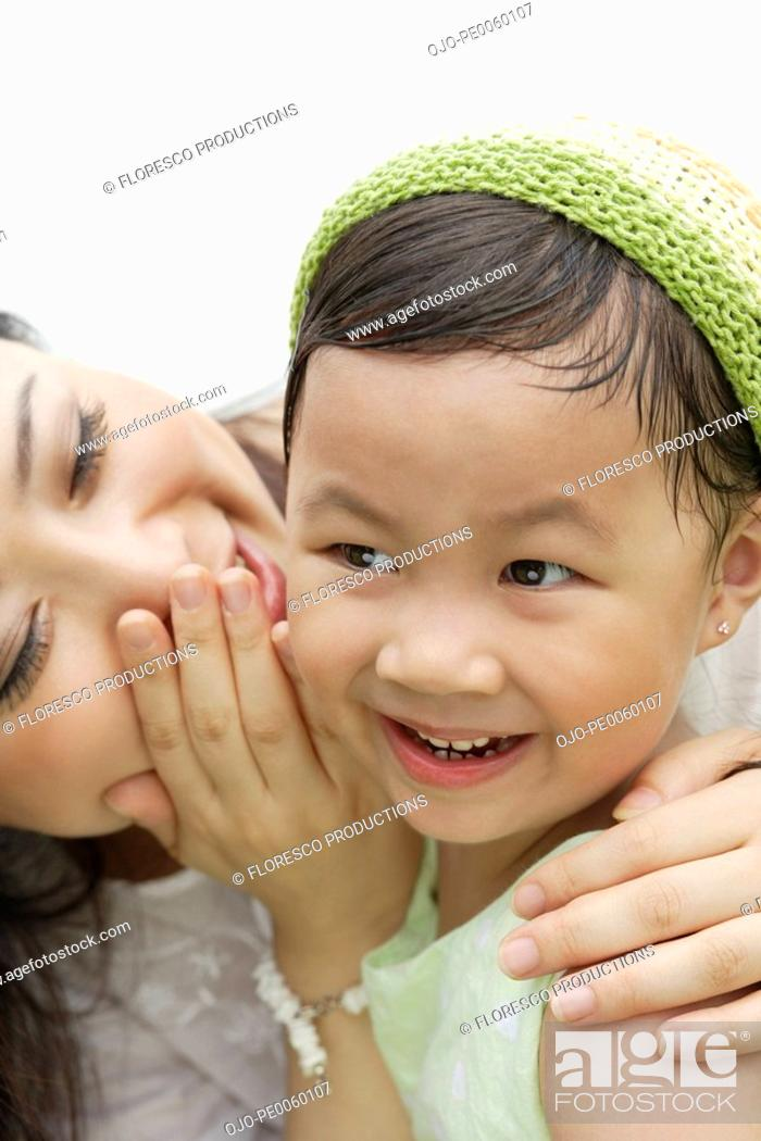 Stock Photo: Woman whispering in young girls ear.