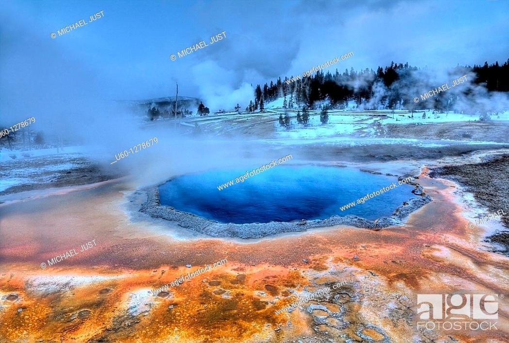 Stock Photo: Crested Pool's colors shine during the winter at Yellowstone National Park as Grand Geyser erupts in the background.