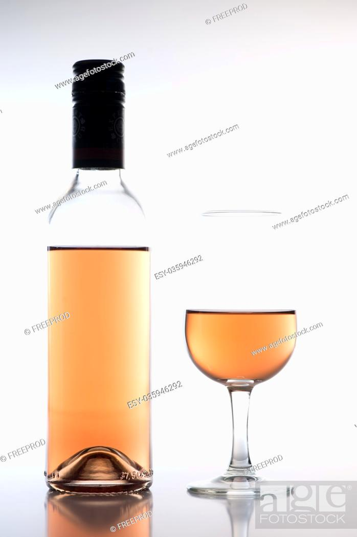 Stock Photo: Rose wine glass and bottle on white background, France.