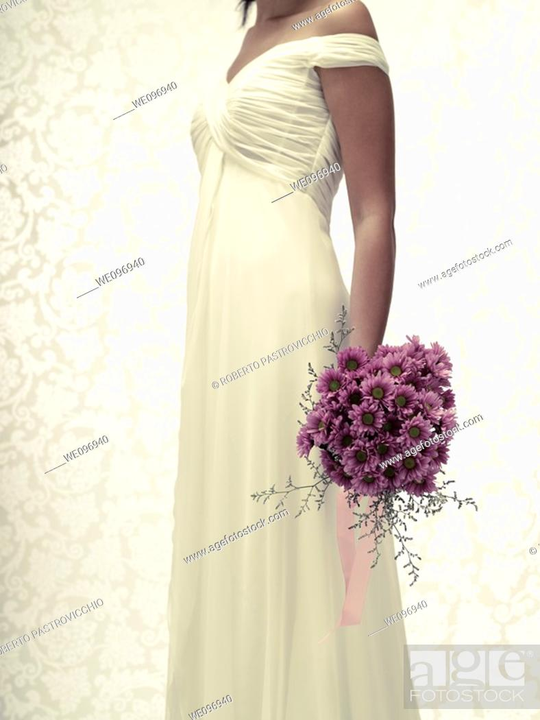 Stock Photo: Bride in a white wedding dress holding a flower bouquet.