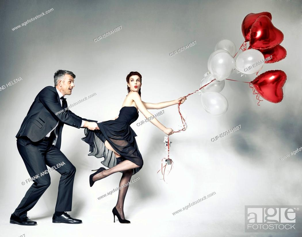 Stock Photo: Man pulling dress of woman with heart-shaped balloons.