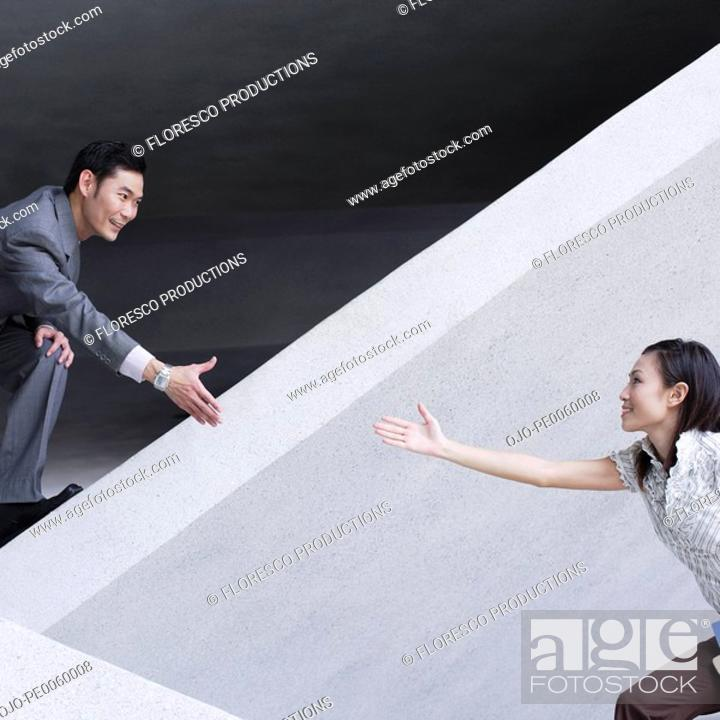 Stock Photo: Businessman helping businesswoman over structure outdoors.