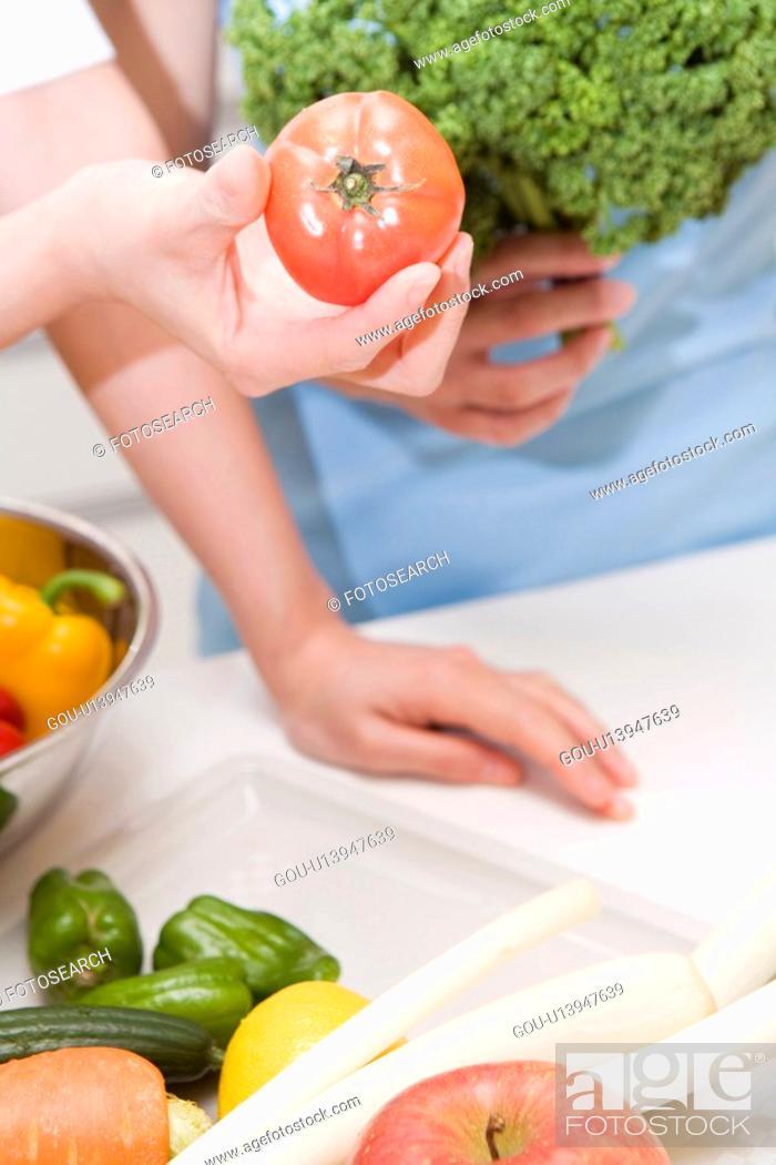 Stock Photo: Hand holding a tomato.