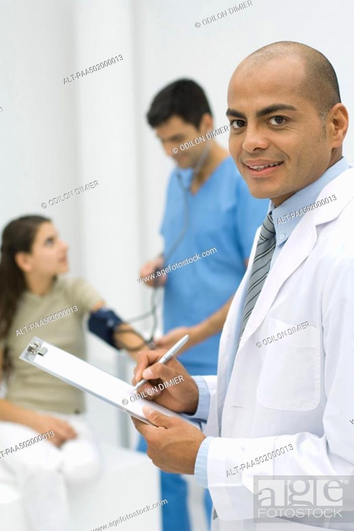 Stock Photo: Doctor writing on clipboard, smiling at camera, nurse measuring patient's blood pressure in background.