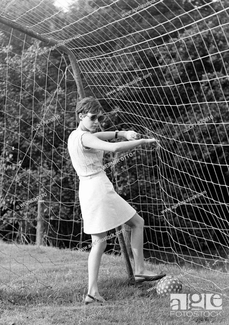 Stock Photo: Sixties, black and white photo, people, young girl stands in a football goal and picks a football out of the net, jersey, sweater, aged 18 to 22 years, Monika.