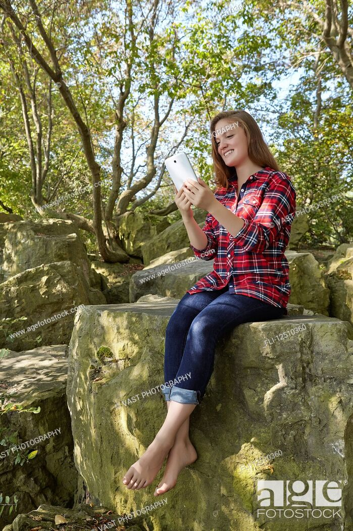 Imagen: A teenage girl wearing jeans and a plaid shirt in bare feet sits on a boulder using her smart phone, Woodbine Beach; Toronto, Ontario, Canada.
