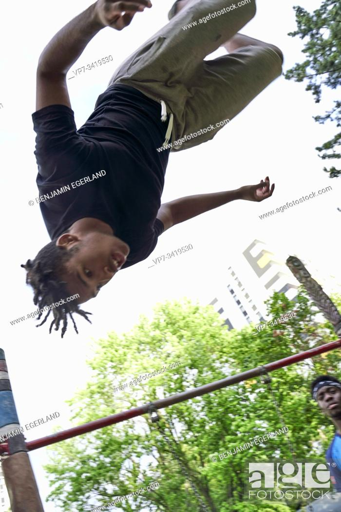 Stock Photo: Young man jumping somersault in park. Frankfurt am Main, Germany.