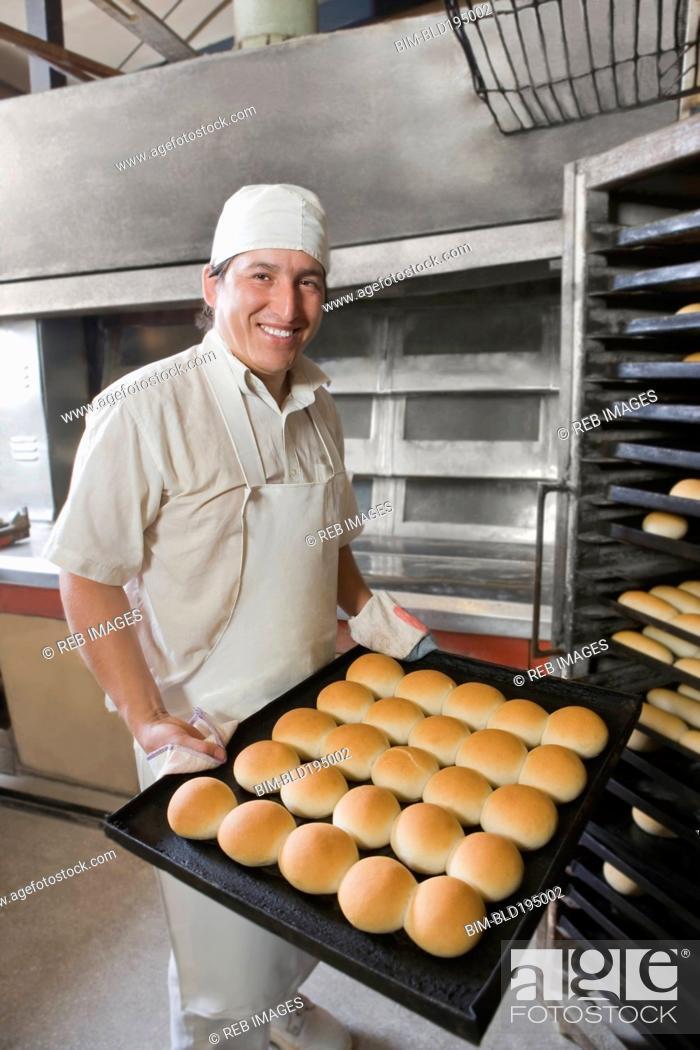 Stock Photo: Hispanic baker holding tray with bread.