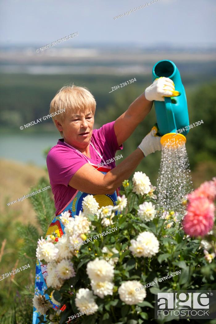 Stock Photo: A woman in a summer blossoming garden.