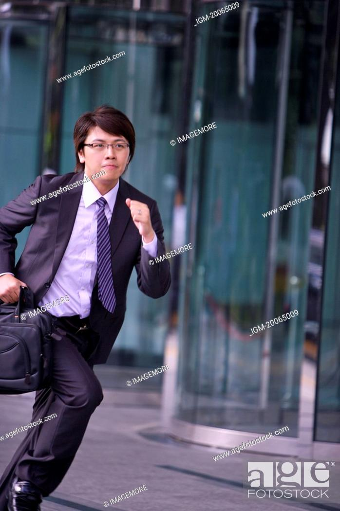 Stock Photo: Young businessman holding briefcase and running.
